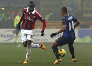 Photo - AC Milan forward Mario Balotelli, left, gets the ball past Inter Milan Colombian midfielder Fredy Guarin during a Serie A soccer match at the San Siro stadium in Milan, Italy, Sunday, Feb. 24, 2013. (AP Photo/Luca Bruno)