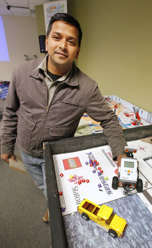 Photo - Ramier Shaik, founder and CEO of techJOYnT, shows a robot students can use at his business, 8328 Glade Ave. Photo by Paul B. Southerland, The Oklahoman ORG