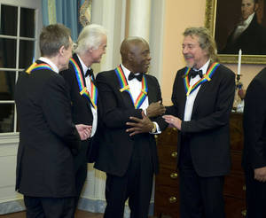 Photo - 2012 Kennedy Center Honorees and members of Led Zeppelin John Paul Jones, left, Jimmy Page, second from left, and Robert Plant, right, talk with fellow 2012 Kennedy Center Honoree Buddy Guy at the end of the State Department Dinner for the Kennedy Center Honors gala Saturday, Dec. 1, 2012 at the State Department in Washington. (AP Photo/Kevin Wolf)