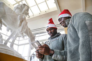 "Photo - U.S. Army Spc. Tingwei Adeck, left, and Pfc. Alexander Shiamgbor look at photos on Adeck's iPad of the two soldiers posing in front of the signature piece of art,  ""End of the Trail"" by  James Earle Fraser,  during their visit to the National Cowboy & Western Heritage Museum. About 150 U.S. Army soldiers stationed at Fort Sill who are not from the area and have no family in town were invited to participate in Soldiers Day Out on Monday, Dec 23, 2013.  The group toured various local museums, stopped to play games and eat in at an arcade. 