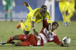 Photo - FC Dallas' Kellyn Acosta, right, takes out Columbus Crew's Dominic Oduro (11) during the first half of an MLS soccer game Sunday, Sept. 29, 2013, in Frisco, Texas. (AP Photo/LM Otero)