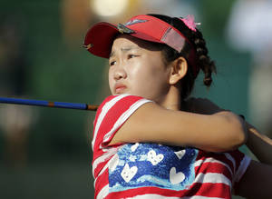 Photo - Lucy Li watches her tee shot on the 14th hole during the first round of the U.S. Women's Open golf tournament in Pinehurst, N.C., Thursday, June 19, 2014. (AP Photo/Chuck Burton)
