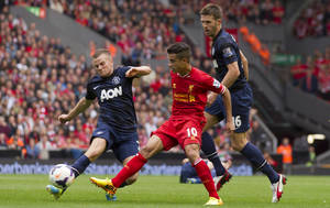Photo - Manchester United's Tom Cleverley, left, clears the ball away from Liverpool's Philippe Coutinho, centre, as Michael Carrick looks on during their English Premier League soccer match at Anfield Stadium, Liverpool, England, Sunday Sept. 1, 2013. (AP Photo/Jon Super)