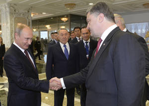Photo - Russian President Vladimir Putin, left, shakes hands with Ukrainian President Petro Poroshenko, right, as Kazakh President Nursultan Nazarbayev, center, looks at them, prior to their talks after after posing for a photo in Minsk, Belarus, Tuesday, Aug. 26, 2014. Leaders of Russia, Belarus, two other former Soviet republics as well as top EU officials are meeting in Minsk, Belarus, for a highly anticipated summit to discuss the crisis in Ukraine which has left more than 2,000 dead and displaced over 300,000 people. (AP Photo/Kazakh Presidential Press Service, Sergei Bondarenko, Pool)