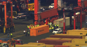 Photo -   This image made from video provided by Eyewitness News WABC-TV shows an aerial view near a container ship in Newark with suspected stowaways. Dock workers rushed to unload containers stacked on top of one another inside a cargo ship that arrived in New Jersey from the Middle East on Wednesday, June 27, 2012 after Coast Guard officials heard knocking from one during a routine inspection, suggesting that stowaways might be on board. (AP Photo/Eyewitness News WABC-TV) MANDATORY CREDIT