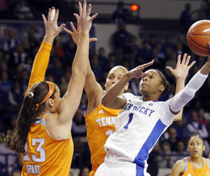 photo - Kentucky's A'dia Mathies (1) shoots next to Tennessee's Taber Spani (13) and Cierra Burdick during the first half of an NCAA college basketball game at Memorial Coliseum in Lexington, Ky., Sunday, March 3, 2013. (AP Photo/James Crisp)