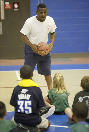 Photo - Coach Jerrame Dockery gives instructions to children during the OCCC Summer Sports Camp on the Oklahoma City Community College campus in southwest Oklahoma City, OK, Monday, June 2, 2014,  Photo by Paul Hellstern, The Oklahoman