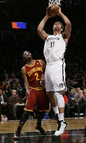 Photo - Brooklyn Nets' Brook Lopez (11) shoots next to Cleveland Cavaliers' Kyrie Irving (2) during the first half of an NBA basketball game Saturday, Dec. 29, 2012, in New York. (AP Photo/Frank Franklin II)