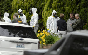 Photo - During the execution of a search warrant, members of the Joint Federal Haz-Mat Team, FBI, and local law enforcement gather in front of the Osmun Apartments near the intersection of First Avenue and Oak Street in Browne's Addition on Saturday, May 18, 2013 in Spokane, Wash. The search warrant is in connection with ricin-laced letters intercepted at a Post Office facility in Spokane earlier in the week. (AP Photo/TheSpokesman-Review, Colin Mulvany) COEUR D'ALENE PRESS OUT