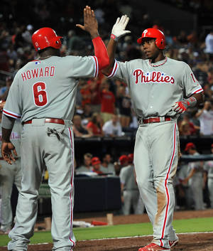 Photo -   Philadelphia Phillies' John Mayberry (15) celebrates his three-run home run against the Atlanta Braves at the plate with teammate Ryan Howard (6) during the tenth inning of a baseball game on Friday, Aug. 31, 2012, at Turner Field in Atlanta. (AP Photo/Gregory Smith)