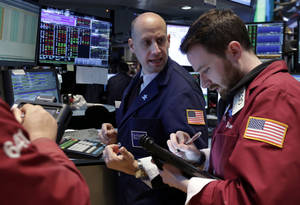 Photo - Specialist Meric Greenbaum, center, works at his post on the floor of the New York Stock Exchange Wednesday, April 30, 2014.  The stock market is edging lower Wednesday after the U.S. economy slowed more drastically in the first quarter than economists had believed. (AP Photo)