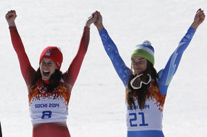 Photo - Women's downhill gold medalists Switzerland's Dominique Gisin, left, and Slovenia's Tina Maze, right, hold hands during a flower ceremony at the Sochi 2014 Winter Olympics, Wednesday, Feb. 12, 2014, in Krasnaya Polyana, Russia.  (AP Photo/Christophe Ena)