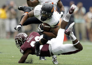 Photo - Oklahoma State's Josh Stewart (5) dives forward as he is tackled by Mississippi State's Kendrick Market (26) during the AdvoCare Texas Kickoff college football game between the Oklahoma State University Cowboys (OSU) and the Mississippi State University Bulldogs (MSU) at Reliant Stadium in Houston, Saturday, Aug. 31, 2013. Photo by Sarah Phipps, The Oklahoman