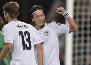 Photo -   Germany's Mesut Oezil, right, celebrates after scoring during the Brazil World Cup 2014 group C qualifying soccer match between Germany and Faroe Islands Friday, Sept. 7, 2012 in Hannover, Germany. (AP Photo/Martin Meissner)