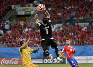 Photo - Chile's goalkeeper Claudio Bravo leaps above Australia's Tim Cahill to claim the ball during the group B World Cup soccer match between Chile and Australia at the Arena Pantanal in Cuiaba, Brazil, Friday, June 13, 2014. (AP Photo/Felipe Dana)