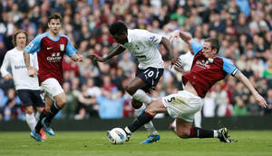 Photo -   Tottenham Hotspur's Emmanuel Adebayor, center, vies for the ball against Aston Villa's Richard Dunne, right, during their English Premier League soccer match at Villa Park, Birmingham, England, Sunday May 6, 2012. (AP Photo/Tim Hales)