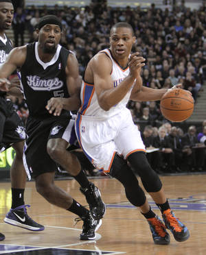Photo - Oklahoma City Thunder guard Russell Westbrook, right, drive against Sacramento Kings forward John Salmons during the first quarter of an NBA basketball game in Sacramento, Calif., Thursday, Feb. 9, 2012. (AP Photo/Rich Pedroncelli) ORG XMIT: SC102