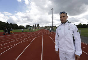 "Photo -   South Africa's sprinter Oscar Pistorius poses for the photographers following his first open training session at the team base during the 2012 Summer Olympics, Sunday, July 29, 2012, in London. Pistorius trained in relative peace and quiet Sunday alongside his South African teammates at a university track in a leafy suburb of west London. It'll get far busier for the history-making ""Blade Runner"" when he does his first formal media appearance Wednesday ahead of becoming the first amputee athlete to run at any Olympics. (AP Photo/Lefteris Pitarakis)"