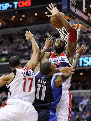 Photo - Dallas Mavericks guard Monta Ellis (11) goes to the basket against Washington Wizards forward Nene, top right, and Garrett Temple (17) during the first half of an NBA basketball game, Wednesday, Jan. 1, 2014, in Washington. (AP Photo/Nick Wass)