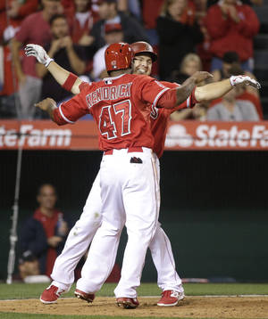 Photo - Los Angeles Angels' J.B. Shuck, facing camera, celebrates his two-run home run with Howie Kendrick during the sixth inning of a baseball game against the New York Mets on Friday, April 11, 2014, in Anaheim, Calif. (AP Photo/Jae C. Hong)