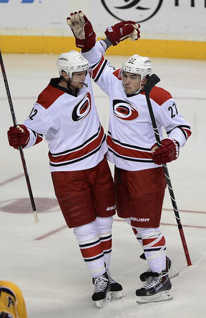 Photo - Carolina Hurricanes center Eric Staal (12) celebrates with defenseman Justin Faulk (27) after Faulk scored a goal against the Nashville Predators in the first period of an NHL hockey game on Thursday, Dec. 5, 2013, in Nashville, Tenn. (AP Photo/Mark Zaleski)