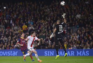 Photo - FC Barcelona's Lionel Messi, from Argentina, left, scores against Rayo Vallecano's goalkeeper Ruben Martinez, right, during a Spanish La Liga soccer match at the Camp Nou stadium in Barcelona, Spain, Saturday, Feb. 15, 2014. (AP Photo/Manu Fernandez)