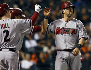 Photo - Arizona Diamondbacks' Willie Bloomquist, right, gets a high five from teammate Aaron Hill after scoring against the San Francisco Giants during the fifth inning of a baseball game, Thursday, Sept. 5, 2013, in San Francisco. (AP Photo/George Nikitin)