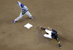 Photo - Los Angeles Dodgers' Dee Gordon, left, forces out Arizona Diamondbacks' Martin Prado while trying to turn a double play on Diamondbacks' Alfredo Marte during the fourth inning of a baseball game on Saturday, May 17, 2014, in Phoenix. Marte was safe. (AP Photo/Matt York)
