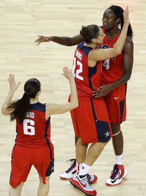Photo -   United States' Tina Charles, top, celebrates with teammates Diana Taurasi, center, and Sue Bird, bottom, during a women's basketball semifinal game against Australia at the 2012 Summer Olympics, Thursday, Aug. 9, 2012, in London. (AP Photo/Victor R. Caivano)