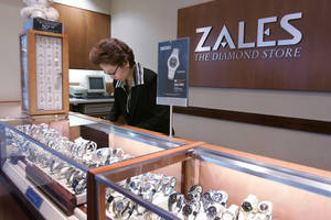 Photo - FILE - In this Jan. 4, 2007, a Zales jewelry store worker looks at watches in San Bruno, Calif.  Signet Jewelers is buying Zale Corp. for approximately $690 million to help diversify its business and expand further internationally. Shares of Zale soared more than 39 percent in Wednesday, Feb. 19, 2014,  premarket trading, while Signet Jewelers Ltd.' stock rose more than 9 percent.  (AP Photo/Paul Sakuma, file)