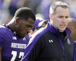 Photo - Northwestern head coach Pat Fitzgerald, right, walks off the field as he talks to wide receiver Rashad Lawrence (17)  after their 20-17 loss to Minnesota in an NCAA college football game in Evanston, Ill., Saturday, Oct. 19, 2013. (AP Photo/Nam Y. Huh)