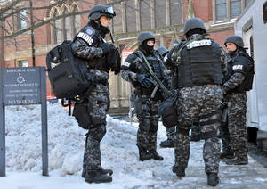Photo - Tactical police assemble outside a building at Harvard University in Cambridge, Mass., Monday, Dec. 16, 2013. Four buildings on campus were evacuated after campus police received an unconfirmed report that explosives may have been placed inside, interrupting final exams. (AP Photo/Josh Reynolds)