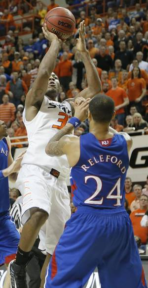 Photo - Oklahoma State 's Marcus Smart (33) puts up a shot over Kansas' Travis Releford (24), Smart fouled out, and was injured on the play, during the college basketball game between the Oklahoma State University Cowboys (OSU) and the University of Kansas Jayhawks (KU) at Gallagher-Iba Arena on Wednesday, Feb. 20, 2013, in Stillwater, Okla. Photo by Chris Landsberger, The Oklahoman