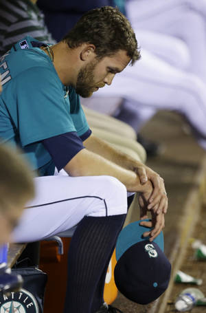 Photo - Seattle Mariners closer Tom Wilhelmsen sits in the dugout after he was pulled from a baseball game against the Houston Astros in the ninth inning, Wednesday, June 12, 2013, in Seattle. (AP Photo/Ted S. Warren)