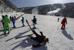 "Photo - In this Saturday Feb. 22, 2014 photo, a North Korean skier falls on the snow at Masik Pass ski resort in North Korea's Masik Pass.  North Korea's newest symbol of national pride and ""single-minded unity,"" the ski resort at Masik Pass, nestled deep in North Korea's eastern mountains, is an impressive site. It has 10 ski runs, from beginning to advanced, a well-equipped rental shop, and a 250-room, eight-story hotel for foreigners alongside a 150-room hotel for Koreans. There's a deluxe swimming pool, lifts up to the top of scenic Taehwa Peak, an underground parking area and a helipad for VIPs or medical emergencies. (AP Photo/Vincent Yu)"