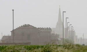 Photo - High winds create a dust haze around a new community, Monday, April 8, 2013 in Gilbert, Ariz. The National Weather Service has issued high wind and blowing dust advisories with wind gusts as high as 60 mph this afternoon and into the early evening. (AP Photo/Matt York)