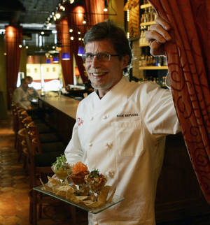 Photo - Chef Rick Bayless poses with a serving of Trio Trio Trio, a sampling of Ceviche Pronterizo, Ceviche Yucateeo and Seaside Cocktail of shrimp and lime-marinated Hawaiian blue marlin at his Frontera Grill restaurant in Chicago. AP PHOTO <strong>Charles Rex Arbogast</strong>