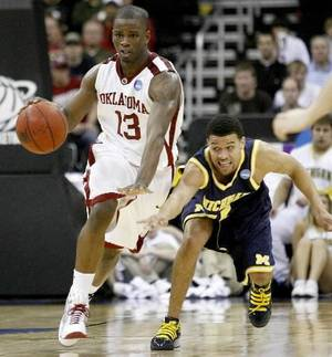 photo - OU's  Willie  Warren brings the ball up the court as Michigan's David Merritt defends during a second-round men's NCAA college basketball tournament game between Oklahoma and Michigan in Kansas City, Mo., Saturday, March 21, 2009. Oklahoma won 73-63. PHOTO BY BRYAN TERRY