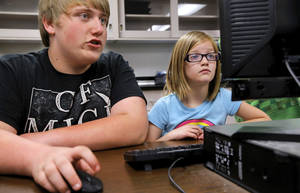 Photo - Billy Wilcox, an eighth grader, helps second grade student Avery Kendrick. Moore Central Junior High students who are enrolled in video game design classes have created math and language learning games using characters from books their neighbors from Plaza Towers Elementary love to read. Students from both schools will get together on Wednesday, May 14, 2014, to play the games and get an opportunity to experience writing CODE.    Photo by Jim Beckel, The Oklahoman