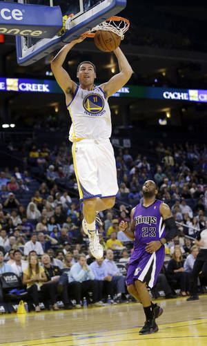 Photo - Golden State Warriors' Klay Thompson dunks past Sacramento Kings' Marcus Thornton (23) during the second half of an NBA preseason basketball game Monday, Oct. 7, 2013, in Oakland, Calif. (AP Photo/Marcio Jose Sanchez)