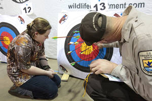 Photo - Delaney Rutledge, 11, South Rock Creek, Shawnee, has her target scored during the Oklahoma's National Archery in the Schools Program State Shoot in the Travel and Transportation Building at the State Fair Park, Wednesday, March 27, 2013. Photo By David McDaniel/The Oklahoman