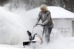 Photo - Lynette Johnson snow blows her Springville,NY,driveway in the bitter wind and cold on,Monday, Jan. 6, 2014.(AP Photo/The Buffalo News, Harry Scull Jr.)