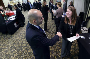 Photo - In this Monday, Feb. 25, 2013, photo, Sayed Mouawad, left, of Providence, R.I., shakes hands with Jillian Wallace of Matix, Inc., during a job fair in Boston. The number of people seeking U.S. unemployment aid fell to a seasonally adjusted 340,000 in the week ended March 2, driving down the four-week average to its lowest level in five years. (AP Photo/Michael Dwyer) ORG XMIT: NYBZ159