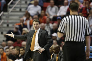 Photo - Oklahoma State coach Travis Ford talks to a referee during the second half in a second-round game against Gonzaga in the NCAA men's college basketball tournament Friday, March 21, 2014, in San Diego. (AP Photo/Gregory Bull)