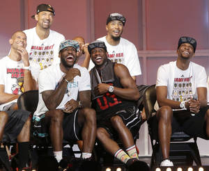 Photo - Miami Heat players laugh as they watch highlights of center Chris Bosh, right, Monday, June 24, 2013, during a celebration for season ticket holders at the American Airlines Arena in Miami. Other players from left are: Shane Battier, Juwan Howard, LeBron James, Dwyane Wade and Rashard Lewis. The Heat defeated the San Antonio Spurs 95-88 in Game 7 to win their second straight NBA championship. (AP Photo/Wilfredo Lee)