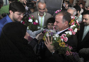 Photo - Iranian scientist, Mojtaba Atarodi, center right, who was in U.S.  custody since late 2011 over allegations he bought high-tech equipment in violation of U.S. sanctions on Iran, is welcomed by his family, upon his arrival at the Imam Khomeini airport outside Tehran, Iran, Saturday, April 27, 2013. Atarodi arrived home via Oman, a Gulf state which has served as a mediator between Washington and Tehran before. (AP Photo/Vahid Salemi)