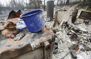 Photo - A few salvageable remains from a house that was destroyed by wildfires on Friday, April 10, 2009, in Choctaw, Okla.  Photo by Chris Landsberger, The Oklahoman