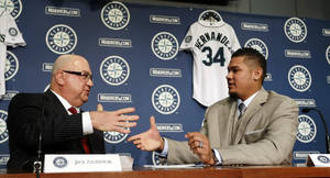 photo - Seattle Mariners' Felix Hernandez, right, shakes hands with general manager Jack Zduriencik after signing a agreement in his new contract to start a news conference, Wednesday, Feb. 13, 2013, in Seattle. Hernandez signed a seven-year contract with the Mariners that makes him the highest-paid pitcher in baseball. The new deal will be worth $175 million. (AP Photo/Elaine Thompson)