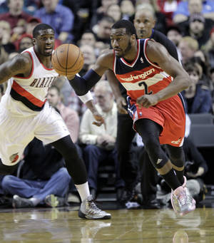 Photo - Washington Wizards guard John Wall, right, races down court after stealing the ball from Portland Trail Blazers guard Wesley Matthews, left, during the first half of an NBA basketball game in Portland, Ore., Thursday, March 20, 2014. (AP Photo/Don Ryan)