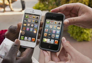 Photo -   Noah Meloccaro, right, compares his older iPhone 4s to the new iPhone 5 held by Both Gatwech, outside the Apple Store in Omaha, Neb., Friday, Sept. 21, 2012 on the first day the iPhone 5 was offered for sale. (AP Photo/Nati Harnik)